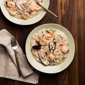 A light green bowl of risotto with calamari rings and other seafood on a dark wood table