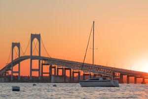 The Newport Bridge at sunset with a sailboat moored in the foreground