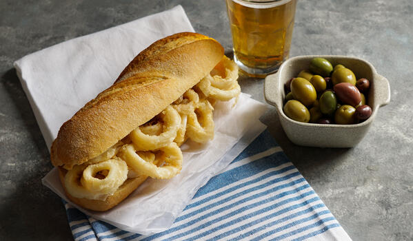A baguette with fried calamari rings, a beer, and small dish of olies