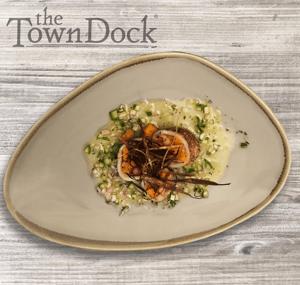 Oblong plate with calamari tubes stuffed with orange squash and shallot vinaigrette