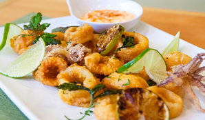 A white plate of fried calamari rings with lime wedges and dipping sauce