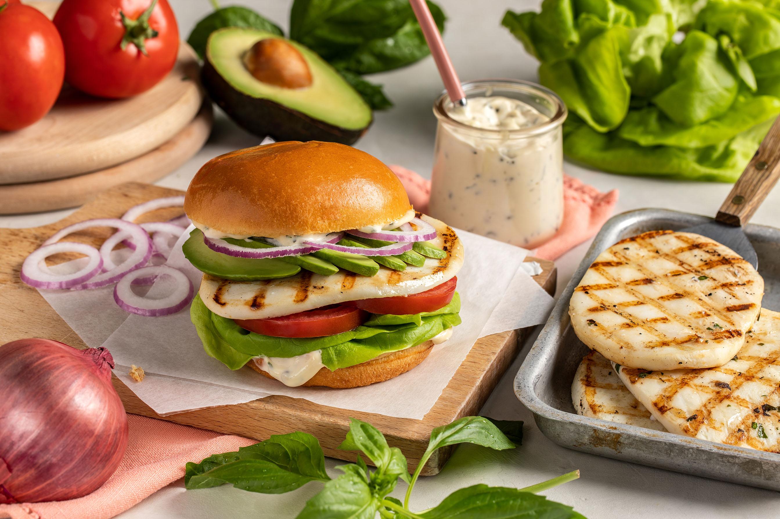 A Calamari Steak burger on a bun with lettuce, onions, avocado, tomato