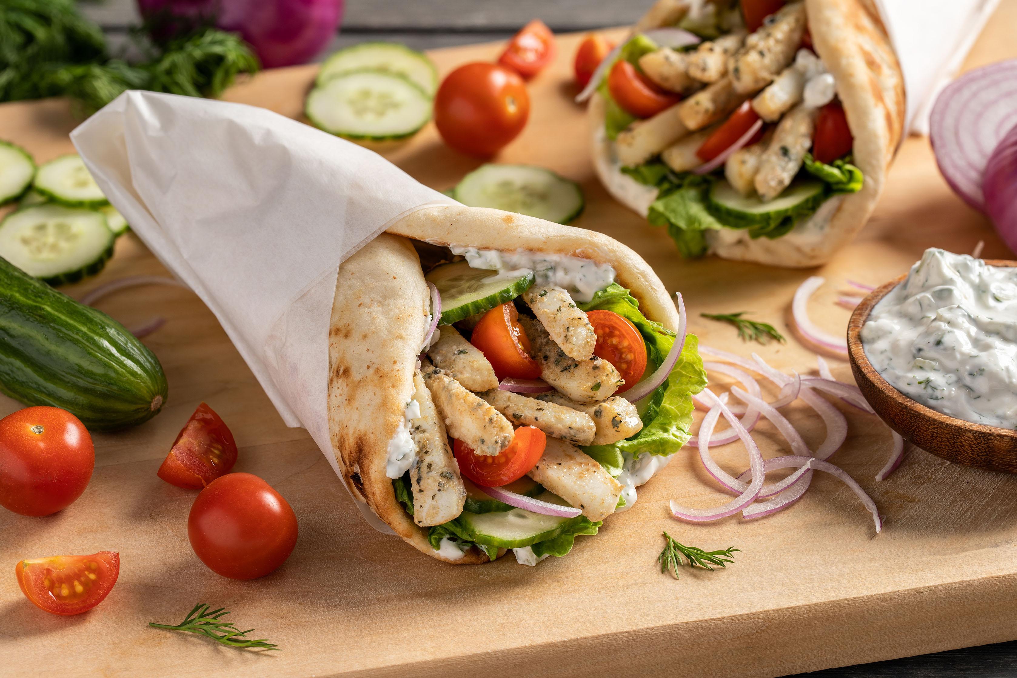 A gyro wrap with calamari strips, lettuce, tomato, red onion, tzatziki sauce